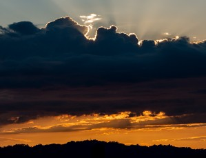 Sun rays behind clouds sunset by Raquel Creative