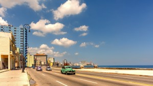 Cars drive along the quay near the ocean on a bright cloudy day by Viktor Birkus