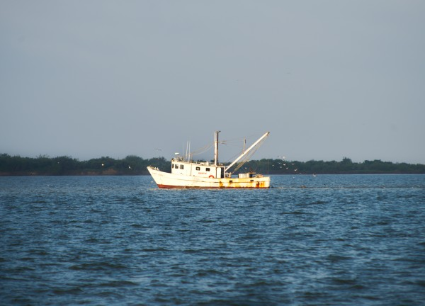 Shrimper in the channel  by Anthony M Farber