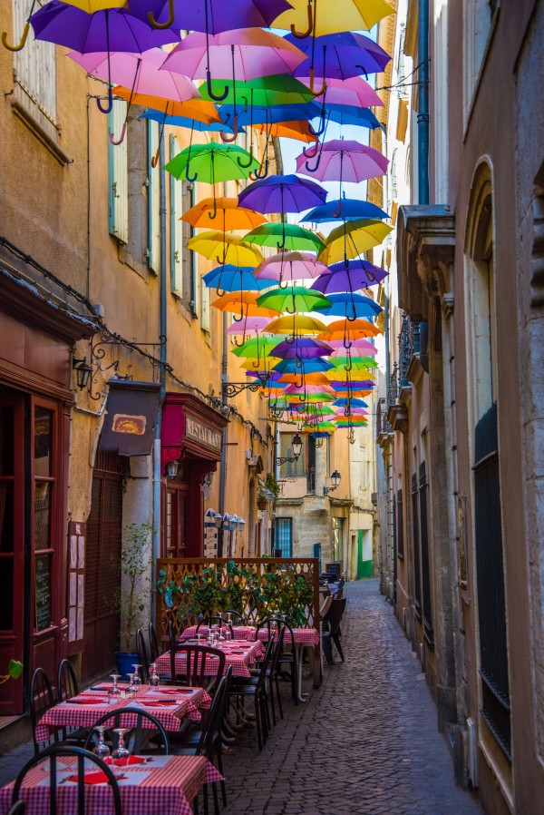 Historic alley and restaurant in Beziers in France in the shade of umbrellas by Francois Lariviere