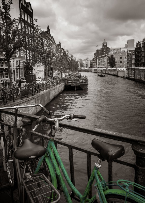 Green bike on the edge of the Amsterdam canal pad by Francois Lariviere