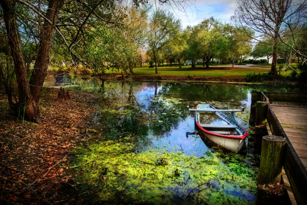 Boat on bayou of Vermillonville historical village by Francois Lariviere