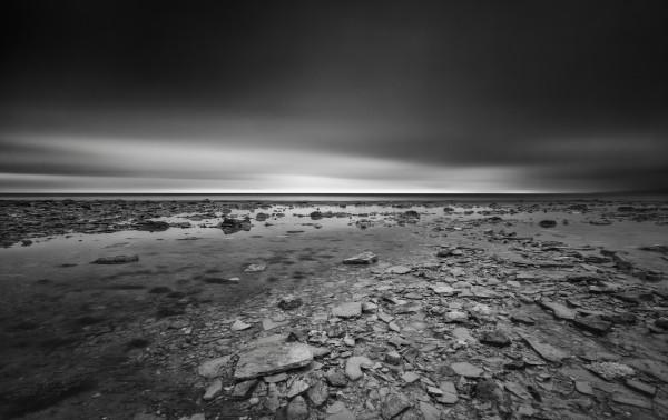 Dramatic sunset at a small bay and rocky beach by Pavel Gospodinov