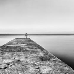 Fisherman angling at sunset by Pavel Gospodinov