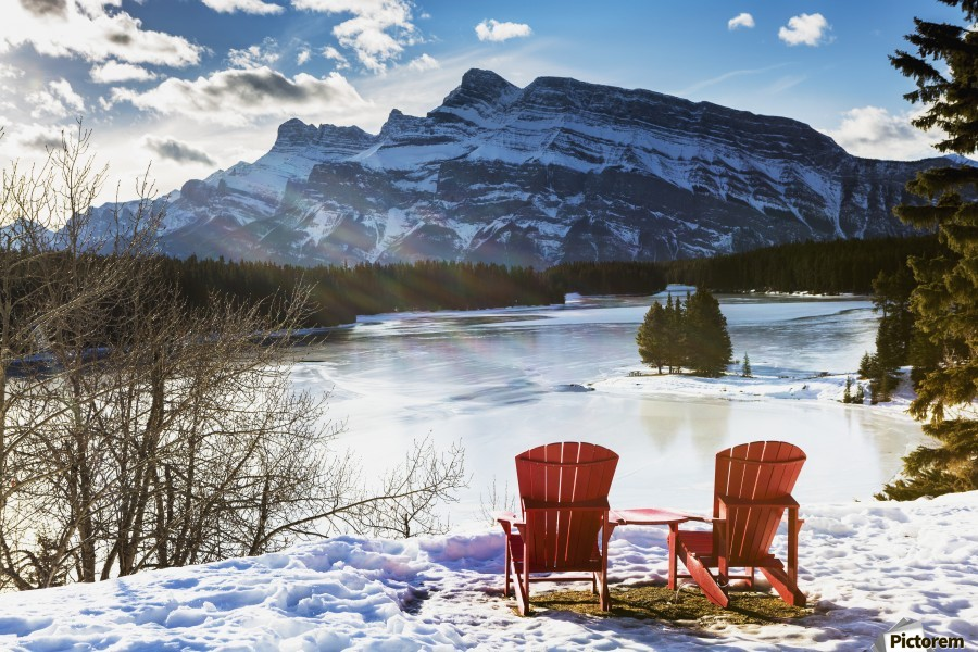 Two red chairs on snow covered ridge overlooking frozen lake with snow covered mountain in the background with blue sky and clouds; Banff, Alberta, Canada  Print