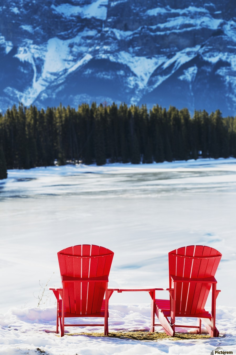 Canvas print & Two red chairs on snow covered ridge overlooking frozen lake with ...