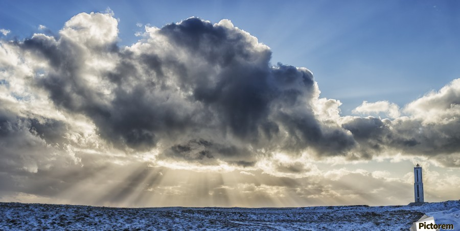 Rays of light shine out from behind the clouds in the skies above a lightnouse along the southern shore of Iceland; Iceland  Print