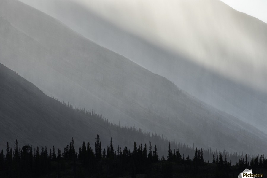 Light shines through the rain as it falls on the mountains along the Wind River in the Peel Watershed; Yukon, Canada  Print
