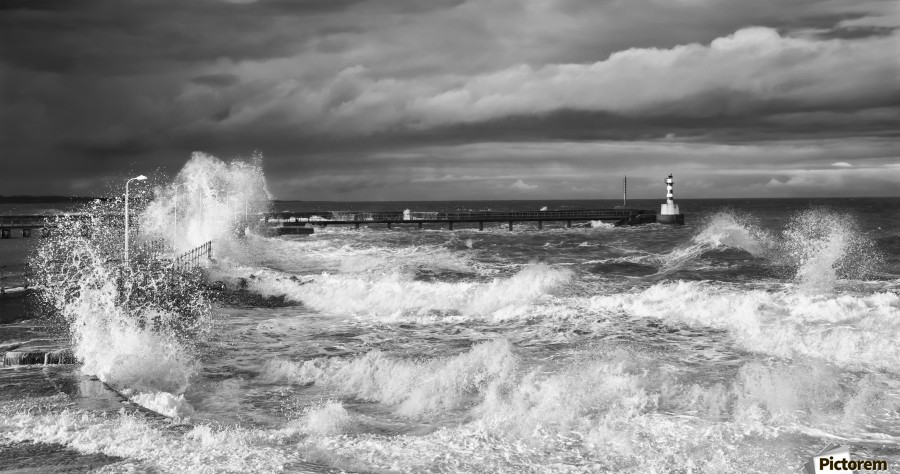 Waves crashing along the coast with a small lighthouse at the end of a pier; Amble, Northumberland, England  Print