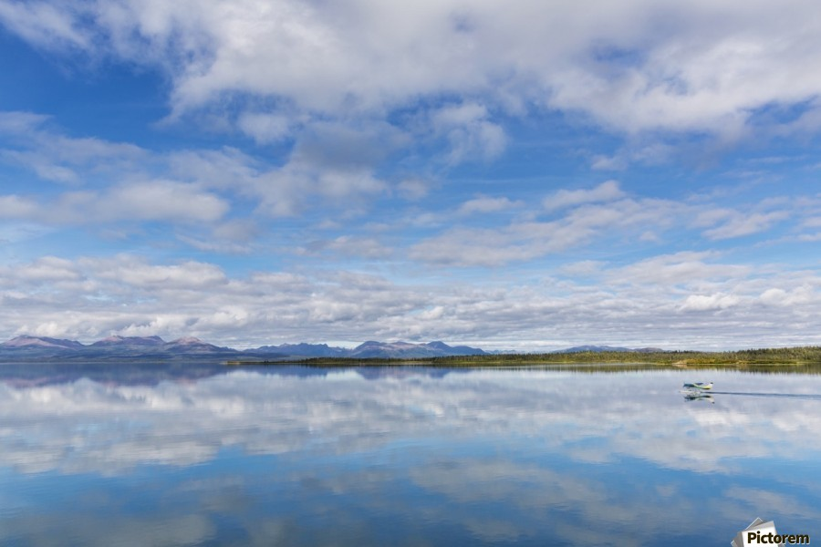 Light clouds reflect on the calm water of Tikchik Lake at the Tikchik Narrows Lodge, Wood Tikchik State Park, Southwestern Alaska; Alaska, United States of America  Print
