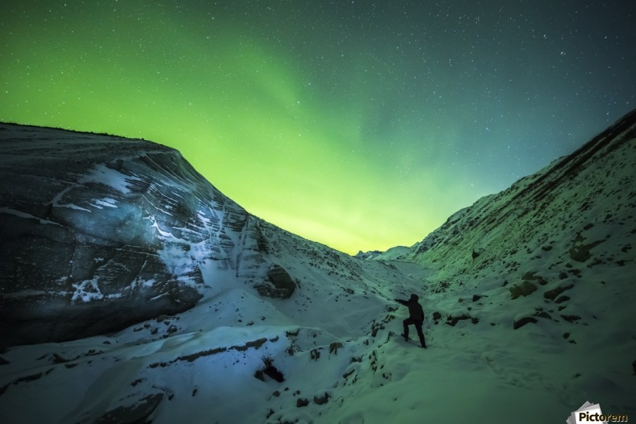 A man lights up the ice of Castner Glacier with a flashlight underneath a diffuse aurora display; Alaska, United States of America  Print