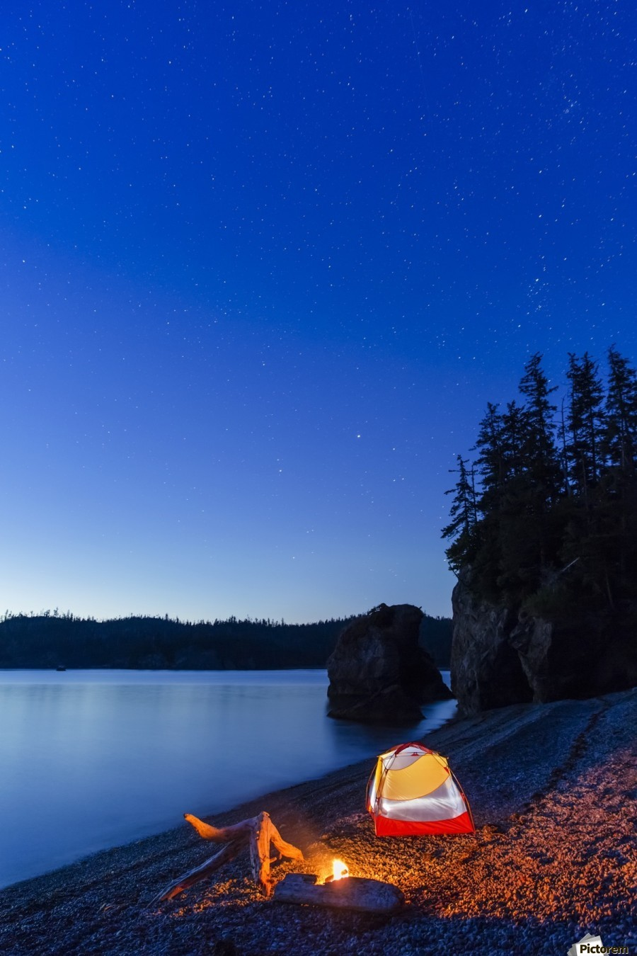 A campfire built on a beach at dusk next to a glowing tent, tranquil ocean water reflecting the warm light, Hesketh Island; Homer, Alaska, United States of America   Print