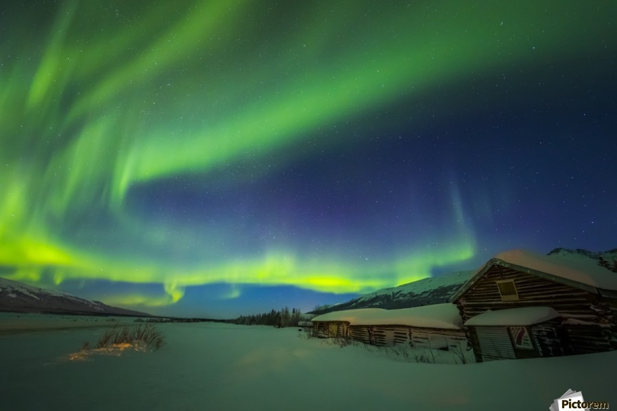The aurora fills the sky above the historic Black Rapids Roadhouse along the Richardson Highway on a bitterly cold night; Alaska, United States of America  Print