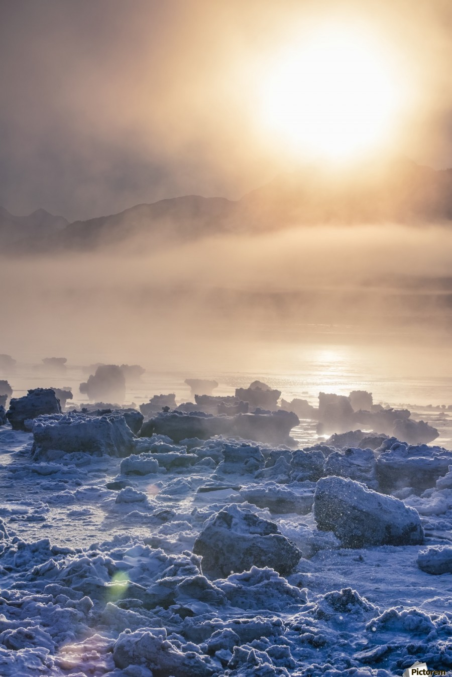Low altitude fog is cast in warm sunset light along Turnagain Arm and the Seward Highway in winter, sea ice covering the ocean in the foreground, the Chugach Moutains revealed in the background, South-central Alaska; Alaska, United States of America  Print