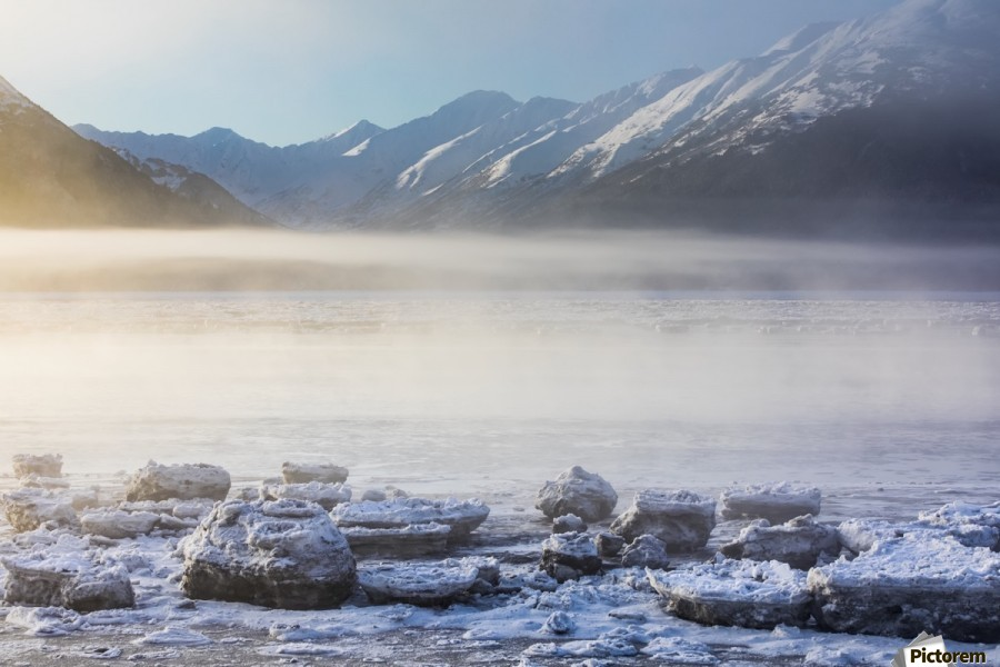 The sun shines through low altitude fog cast in warm light along Turnagain Arm and the Seward Highway, sea ice covering the ocean in the foreground, the Kenai Moutains revealed in the background, South-central Alaska; Alaska, United States of America  Print
