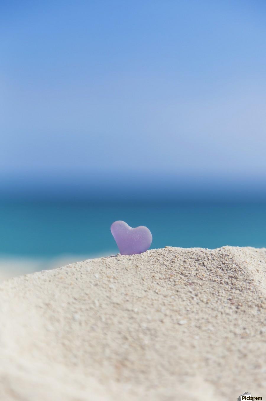 A lavender heart shaped sea glass in the sand at the beach; Honolulu, Oahu, Hawaii, United States of America  Print