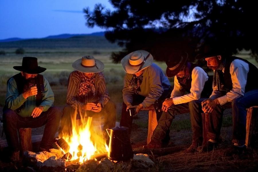 Group Of Cowboys Around A Campfire