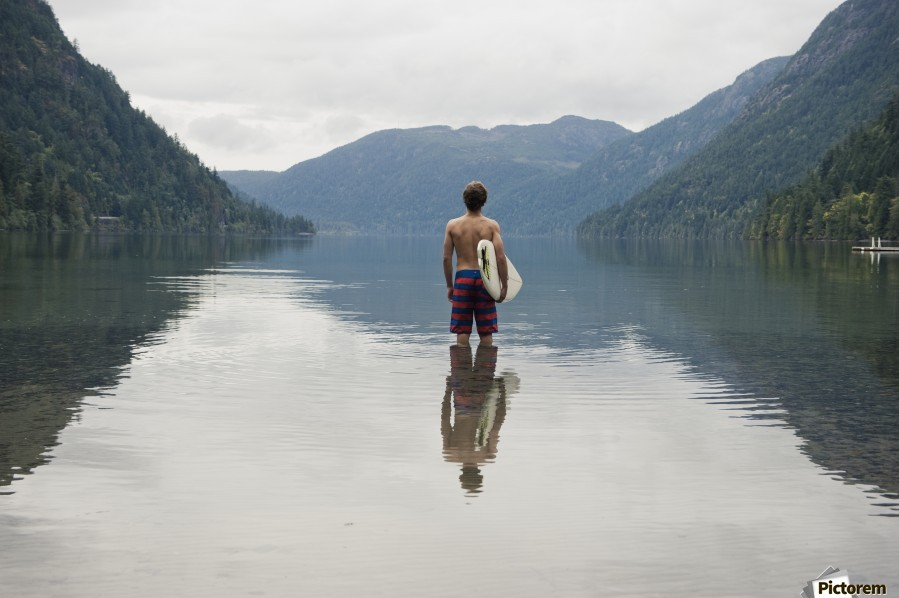 A Young Man Wearing A Swimsuit Stands In Cameron Lake; British Columbia Canada  Print