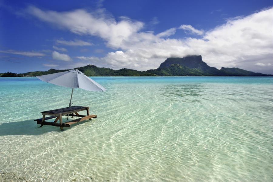 French Polynesia, Tahiti, Bora Bora, Picnic Table And Umbrella In Clear Lagoon Water.  Print