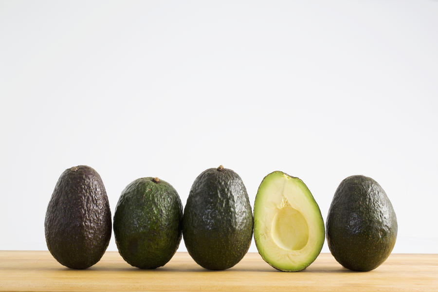 A Row Of Avocados Standing Upright On A Wooden Board With One Cut In Half Without The Pit; Calgary, Alberta, Canada  Print