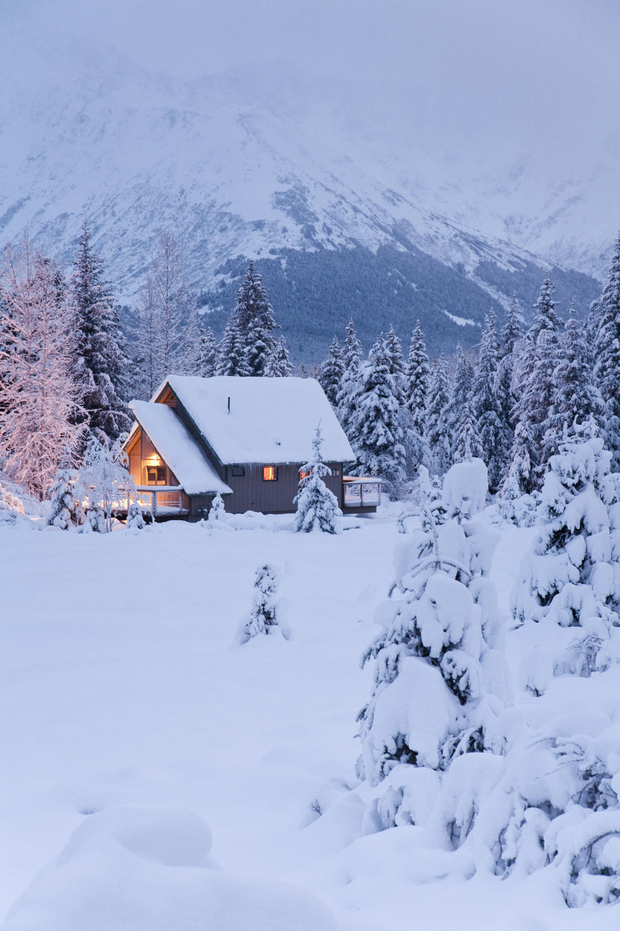 Snowcovered Home In A Wintry Meadow At Dawn With Inside Lights On, Girdwood, Southcentral Alaska  Print