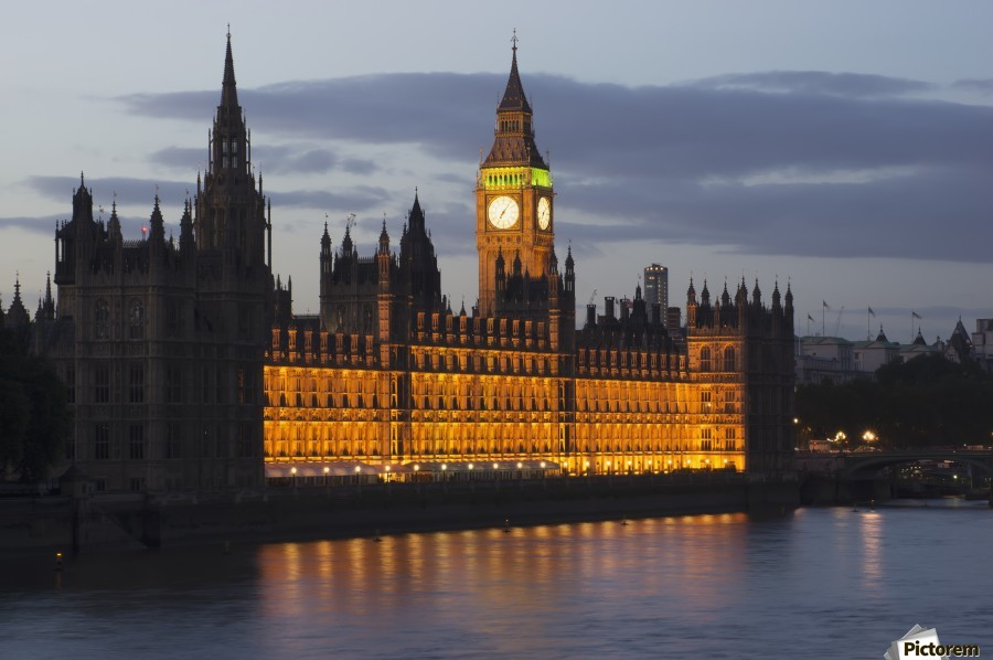 A Building And Clock Tower Along The Water's Edge Illuminated At Dusk; London, England  Print