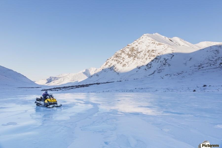 Native youth riding Snowmachine on overflow ice, Inukpasugruk (Giant) Creek, Anaktuvuk Pass, Gates of the Arctic National Park, Brooks Range, Northern Alaska, USA.  Print