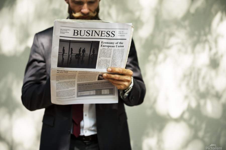 A bearded man reading the business section of a newspaper  Print