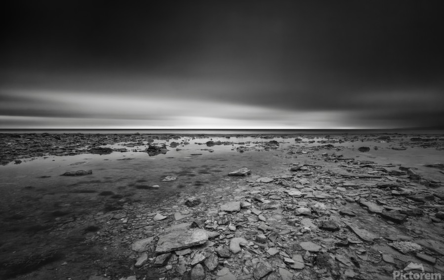 Dramatic sunset at a small bay and rocky beach  Print