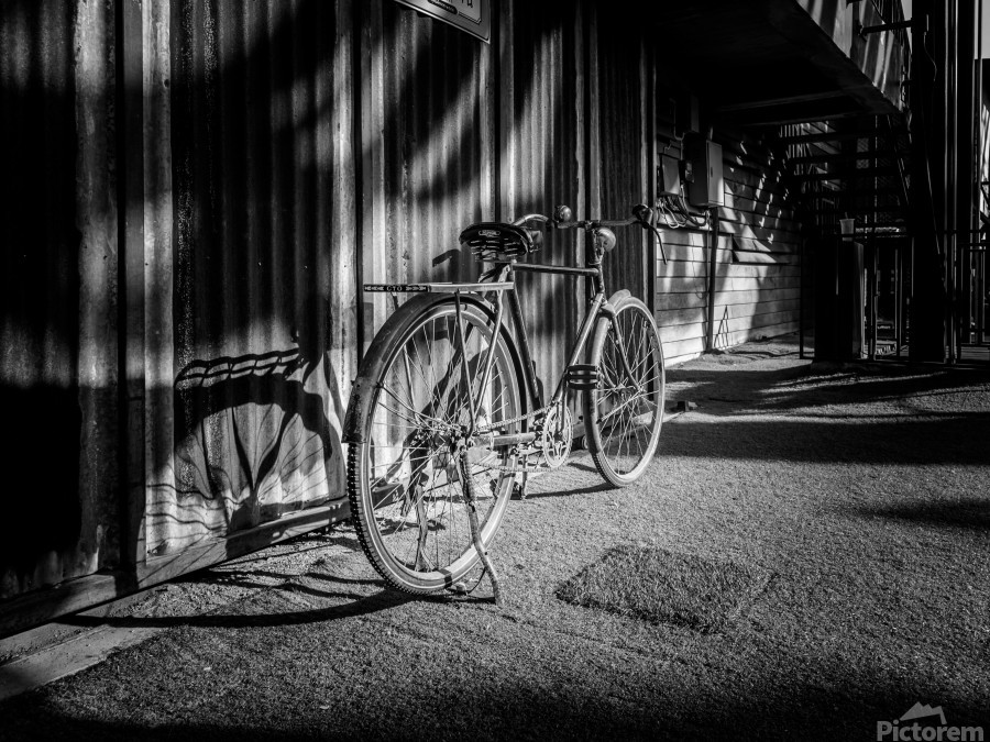 Bicycle parked against the building black and white  Print