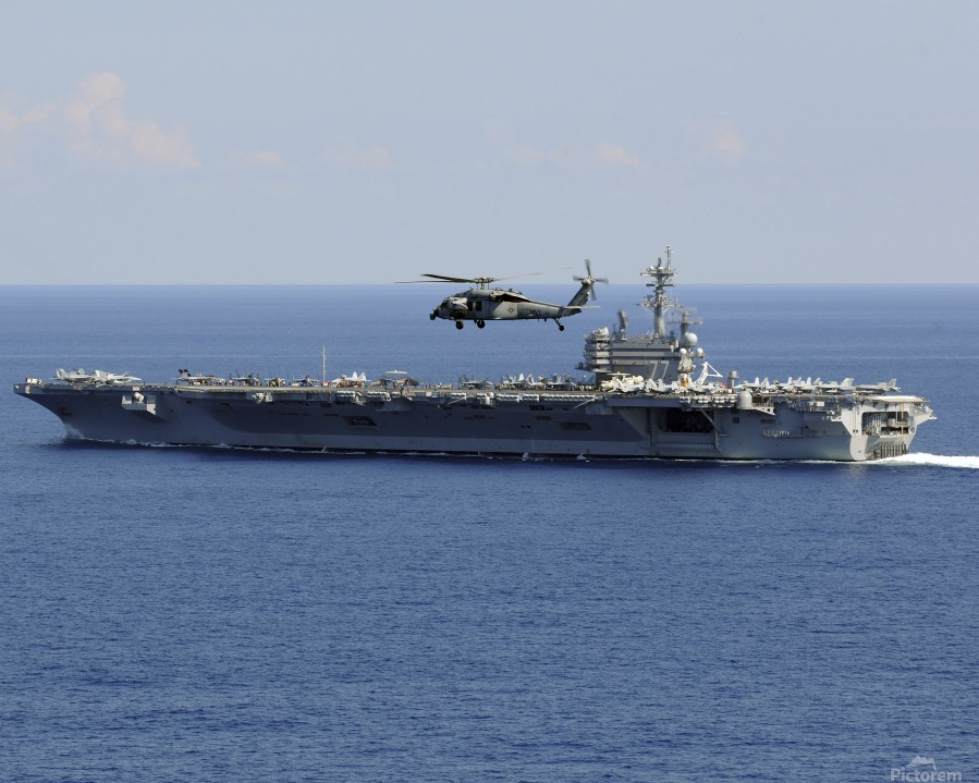 An MH-60S Seahawk helicopter flies over USS George H.W. Bush.  Print