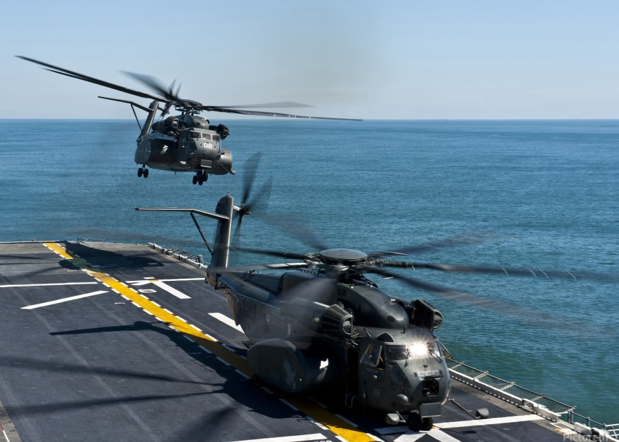 MH-53E Sea Dragon helicopters take off from the flight deck of USS Wasp.  Print