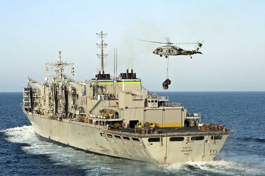 An MH-60S Knighthawk lifts cargo from the fast combat support ship USNS Rainier.  Print