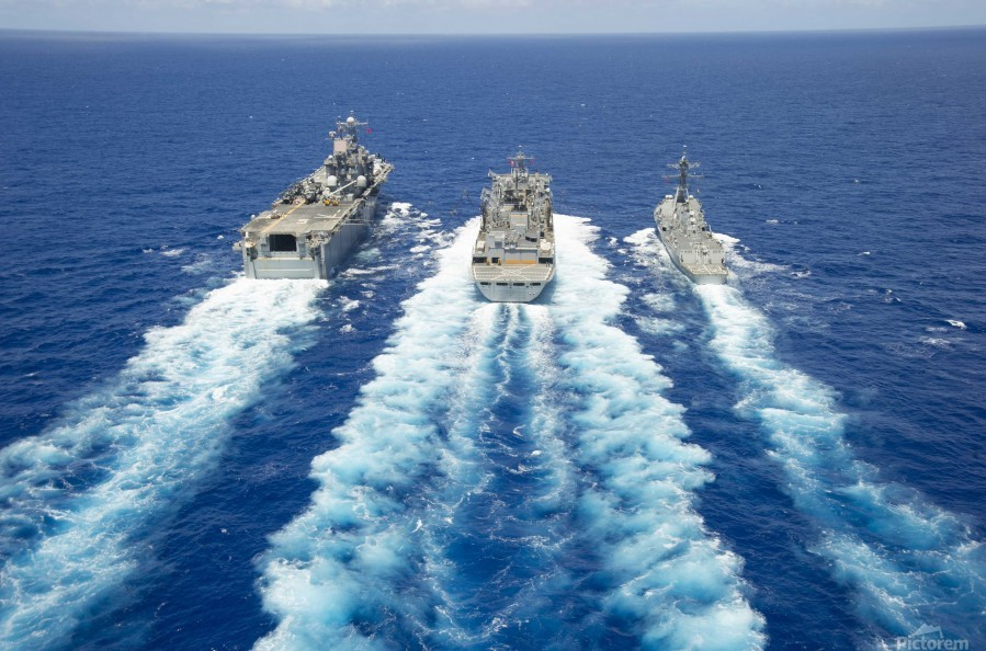 USS Peleliu and USS Spruance conduct a replenishment at sea with USNS Rainier.  Print