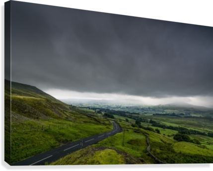 Dark storm clouds over a lush, green landscape and road; North Yorkshire, England  Canvas Print