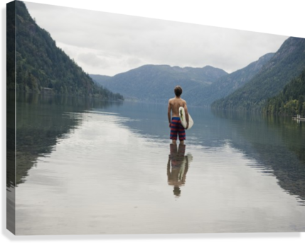 A Young Man Wearing A Swimsuit Stands In Cameron Lake; British Columbia Canada  Canvas Print