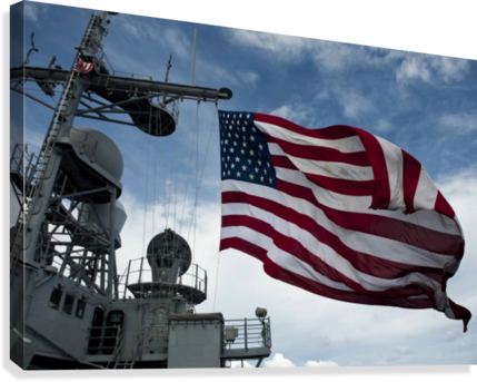 USS Cowpens flies a large American flag during a live fire weapons shoot.  Canvas Print