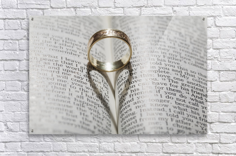 Close up of a gold ring with the shadow of an heart on book about love;Calgary Alberta Canada  Acrylic Print