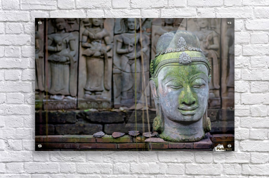 A terra cotta head of buddha sits in front of bas-relief in a terra cotta garden; Chiang Mai, Thailand  Acrylic Print