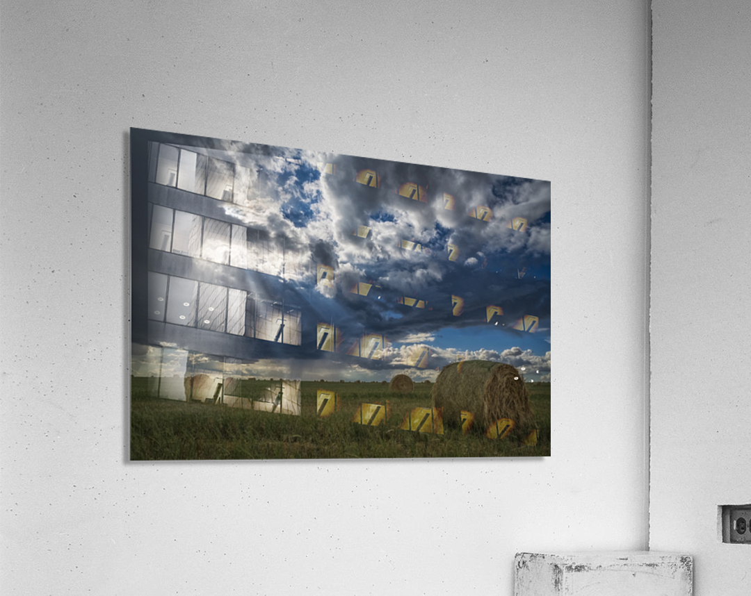 Sunlight breaks through the storm clouds over a field of hay bales; Saskatchewan, Canada  Acrylic Print