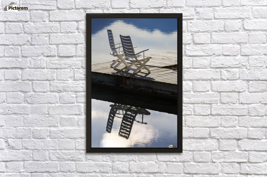 Two white wooden deck chairs on wooden boat dock reflecting in the ...