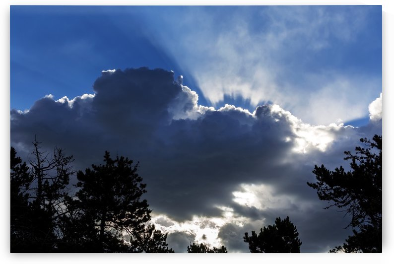 Dramatic backlit cloud covered sky with sun rays beaming through the opening; Waterton, Alberta, Canada by PacificStock