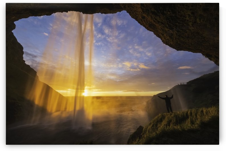 Man standing behind the waterfall known as Seljandafoss along the southern coast of Iceland; Iceland by PacificStock