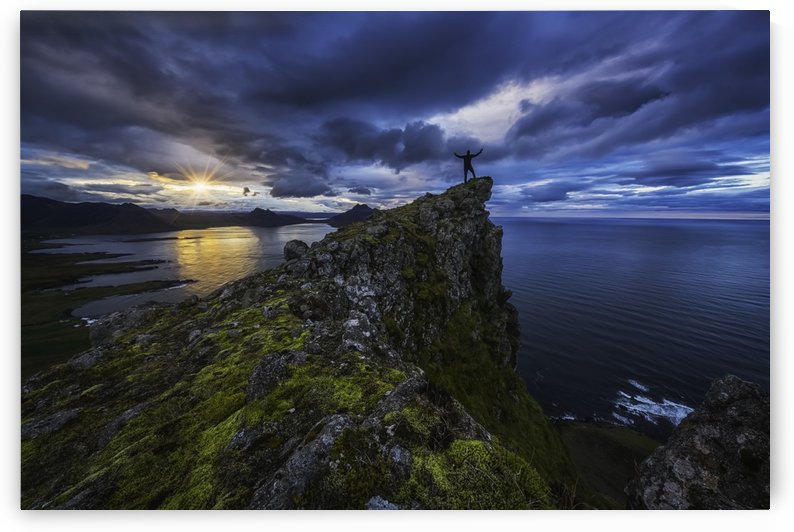 Man standing on top of a sea cliff at sunset along Iceland's Strandir Coast in the West Fjord region; Iceland by PacificStock