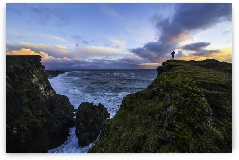 Person standing on a cliff face while the Atlantic Ocean pounds the shores beneath them; Iceland by PacificStock