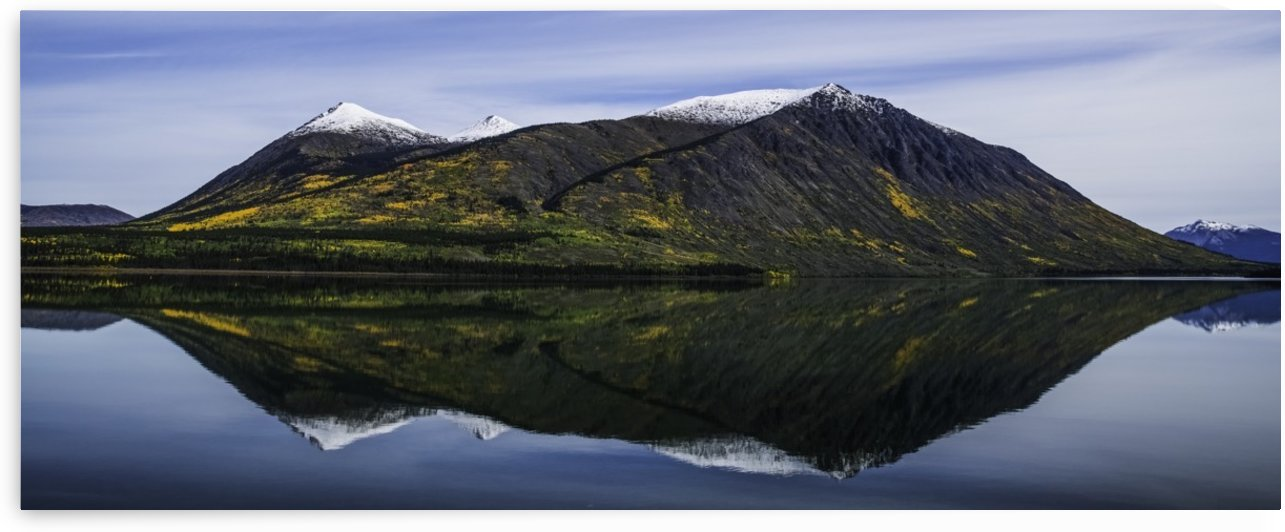 Reflection of the mountains surrounding Carcross reflected in the still waters; Yukon, Canada by PacificStock