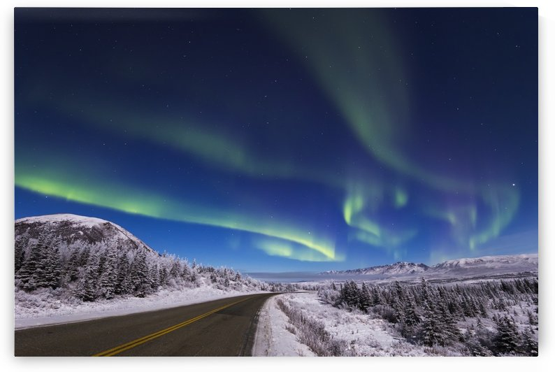 The aurora borealis glows over the Richardson Highway near Donnelly Dome (at left), south of Delta Junction; Alaska, United States of America by PacificStock