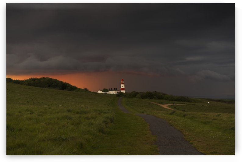 Souter Lighthouse along the coast under ominous storm clouds; South Shields, Tyne and Wear, England by PacificStock