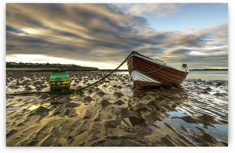 A wooden boat tied to the shore sitting on wet sand at the water's edge at sunset; Whitburn, Tyne and Wear, England by PacificStock