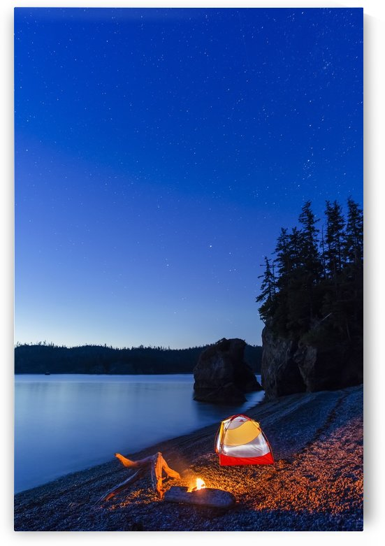 A campfire built on a beach at dusk next to a glowing tent, tranquil ocean water reflecting the warm light, Hesketh Island; Homer, Alaska, United States of America  by PacificStock